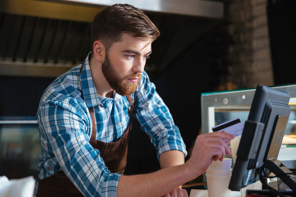 Handsome concentrated bearded waiter swiping credit card through the computer terminal in cafe